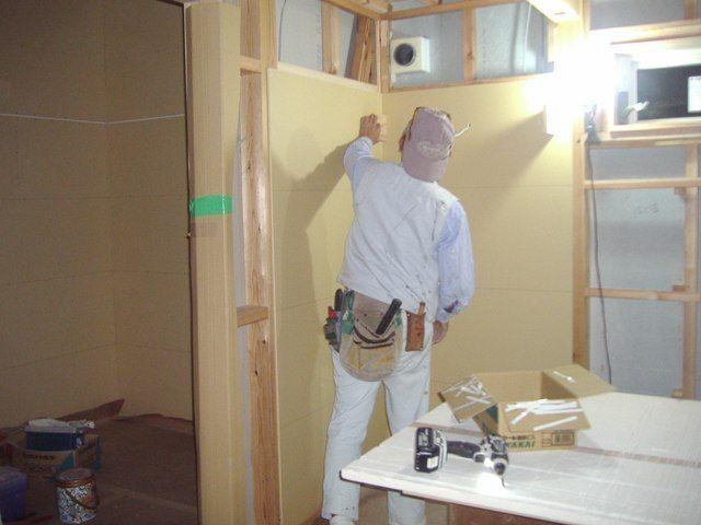 国分の家・現場で大工さんの壁貼り