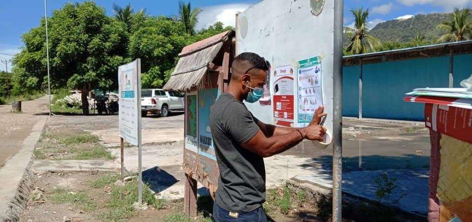 村の中心にある掲示板にポスターを張るシェアスタッフ