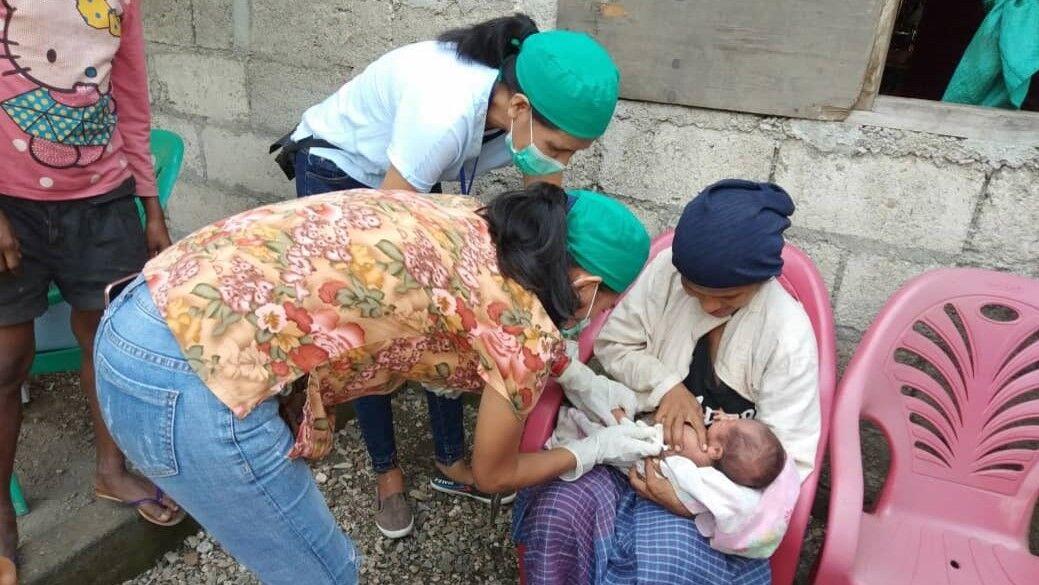 家庭を訪問して予防接種を行う保健スタッフ