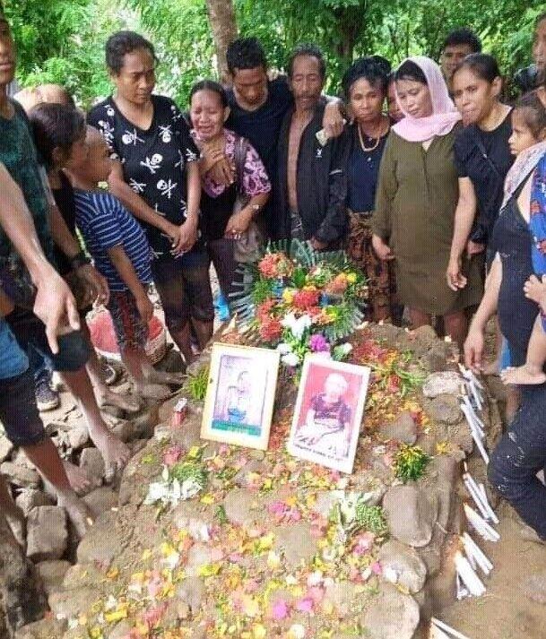 お墓に埋葬され故人を偲ぶ家族たち(東ティモールは土葬)