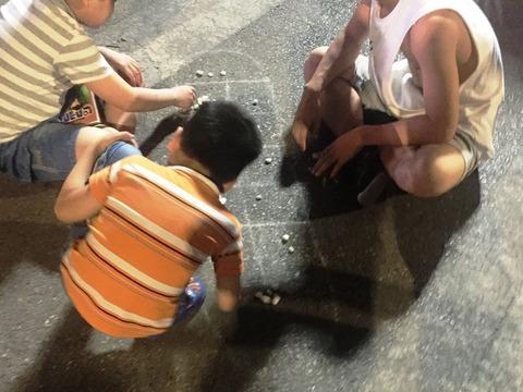 地面に座って石を並べて遊ぶゲーム(名称不明)