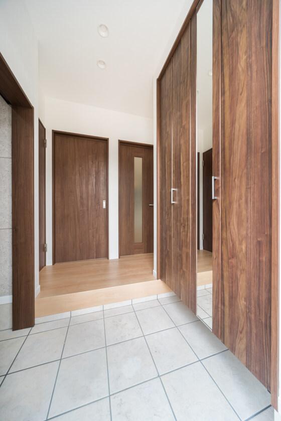 天井の高さまであるシューズクローゼット。扉はミラー付き。パナソニックのベリティス(ウォルナットカラー)。