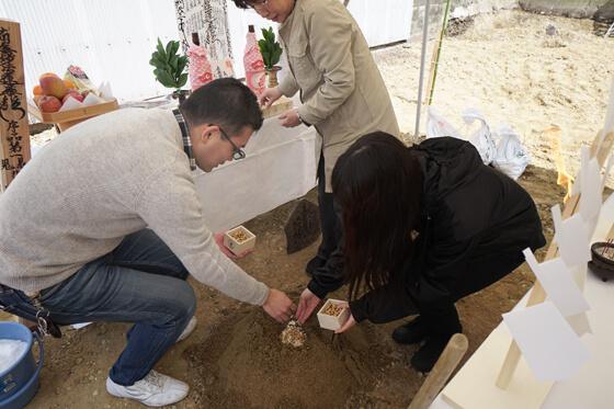 祭壇の前に用意した盛土に「五穀」を撒いているところ。