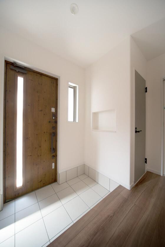 玄関のタイルは「LIXILのフィネッツァ(FN-11)」。綺麗な白です。玄関扉は「ジエスタのC16型(アシリッシュパイン)」。