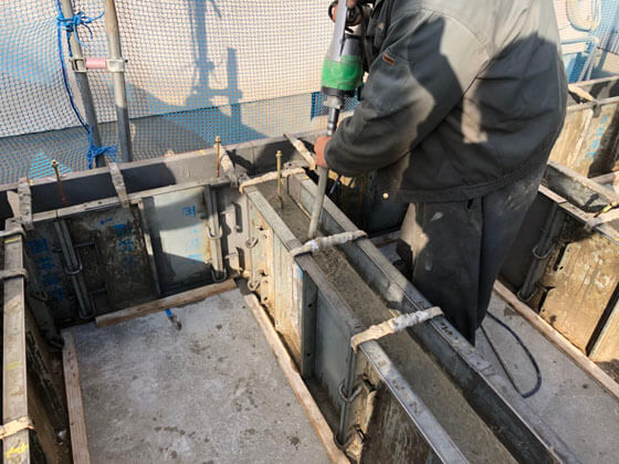 型枠の中にまんべんなくコンクリート充填。コンクリート内にバイブレータを挿入してコンクリートの締固めを行います。