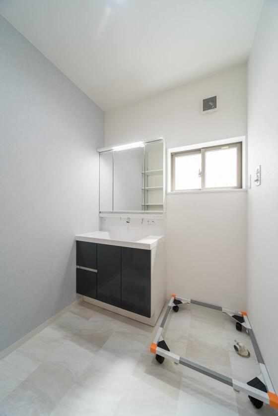 洗面台は「リクシルのMV(扉はディープグレー)」。LEDの照明がとてもシャープな三面鏡洗面台です。洗濯機台はキャスター付き。