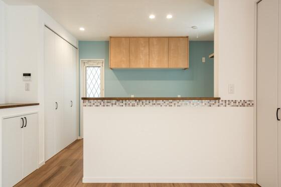 キッチンの裏側を隠す腰壁には、名古屋モザイクのシエルグラスを。食器棚や冷蔵庫を置く面には、水色のアクセントクロスをもってきました