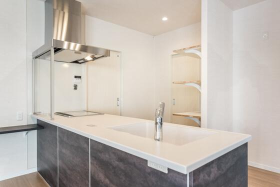 コンロ横の扉が洗面室への入り口、後ろの扉がパントリーへの入り口、パントリーの左右にそれぞれ食器棚と、棚に家電などを置くようになっています