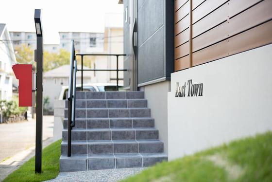 アプローチ階段のタイルは、ニッタイのロマー二95番。天然石のような色むらが美しい黒いタイルです。手摺のブラックがまた映えますね