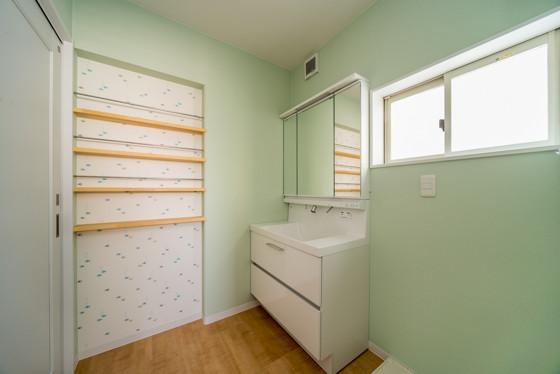 爽やかなミントグリーンの壁紙に包まれた洗面室