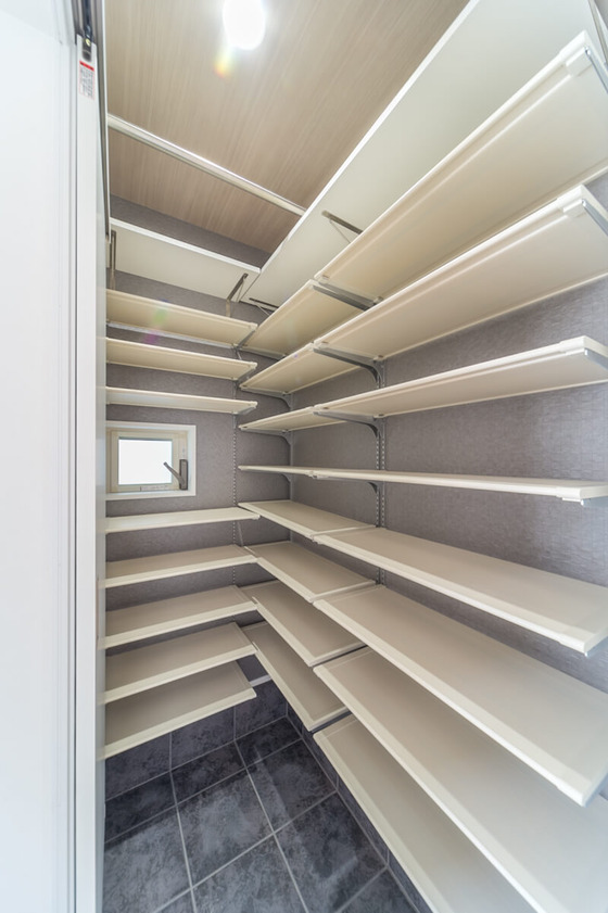 白い靴棚のシューズクローク 南海プライウッドの「靴棚用樹脂棚板」と「背面棚柱+棚受け金物」