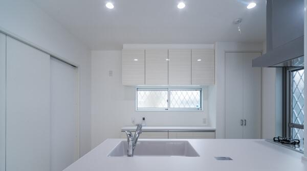 ワイドなカウンター越しに見た、清潔感のある白いキッチン廻り。明るいキッチンスペースです