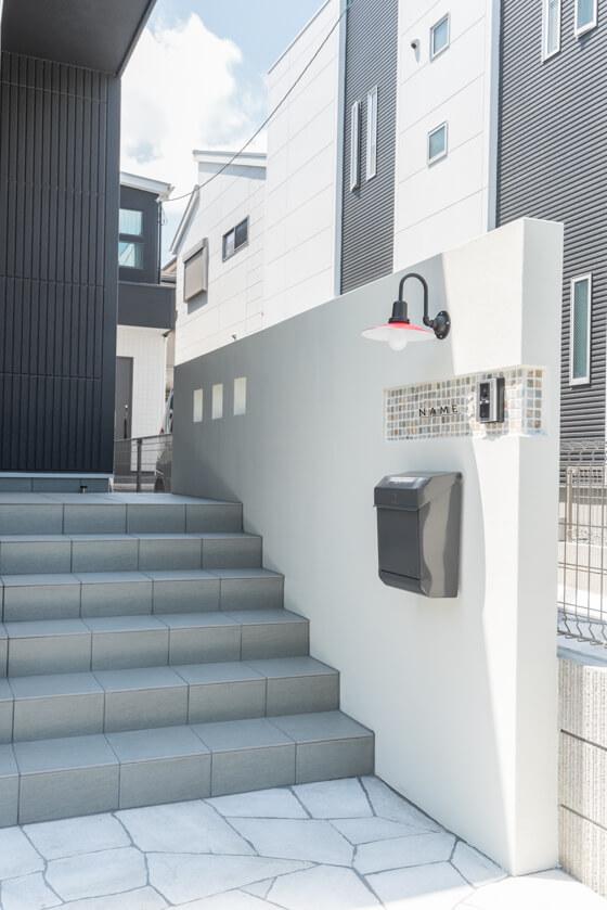 階段とポーチには、ライムアレーナLN-13というグレーのタイルを使用。門柱はすこし凹ませてタイル貼りに。アイランドのモザイクストーン、ナチュラル色です