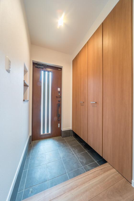 玄関ドアは明るい採光がとれるデザイン、リクシルの「E11型(旧品番)タッチキー付(ポートマホガニー色)」。
