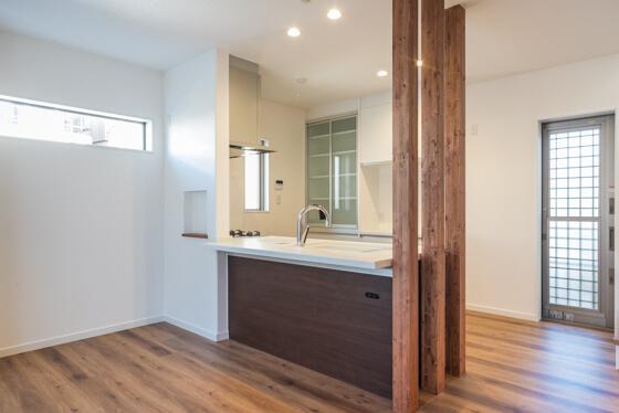 キッチンはパナソニックのラクシーナ。LDKの入り口ドアと合わせたダーク柄のキッチンは、セミフラット対面タイプにして開放感のある仕上がりに