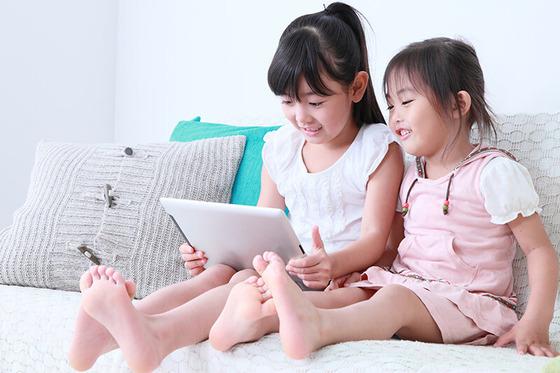 子供2人がタブレットをもちネットを見ているところ
