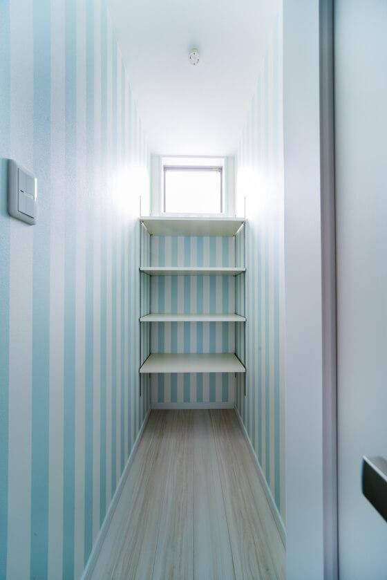 こちらは半畳分のスペースの脱衣室になります。壁のクロスはブルーのストライプ柄です。