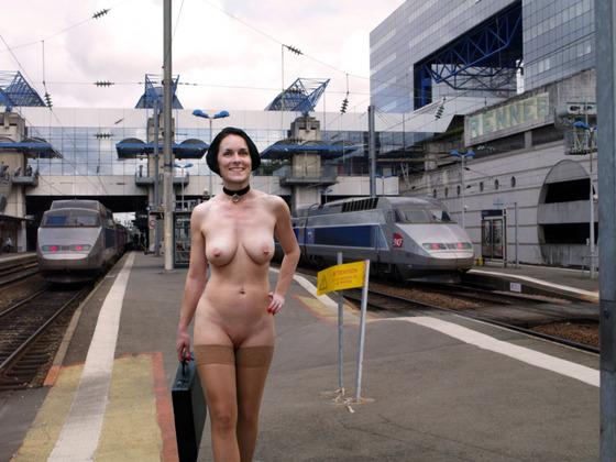 全裸にストッキングだけの姿で駅のホームを歩くパイパン女性の野外露出画像
