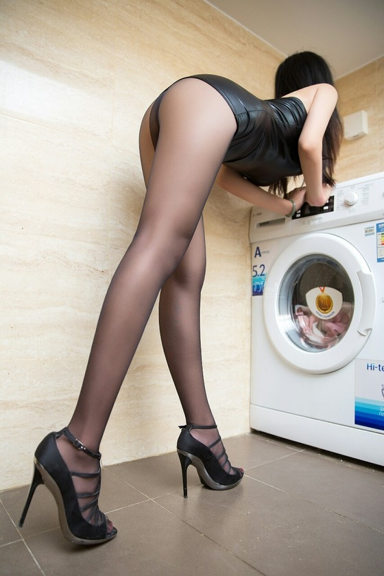 黒パンスト直穿きで乾燥機を操作している女性