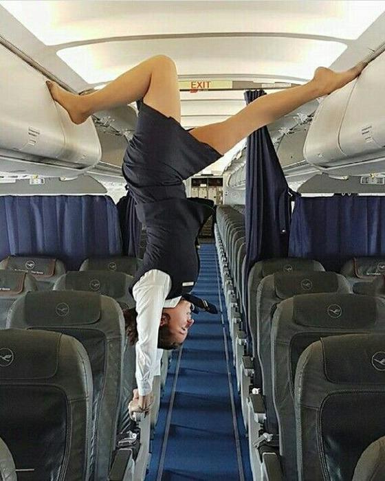 飛行機のなかで逆立ちしているベージュパンストのスチュワーデス