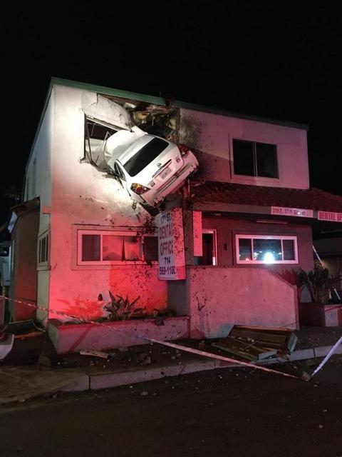 【米国】猛スピードで走っていた車が衝突して跳ね上がり、建物の2階にめり込む事故