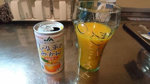 グラスにみかんジュースを注ぐ
