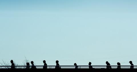 橋の上を歩くスーツ姿の沢山のサラリーマン