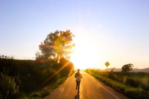 夕日の道をランナーが走る