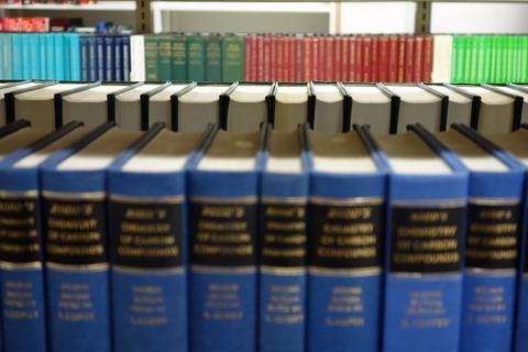 大型本棚に並べられた青い沢山の辞典