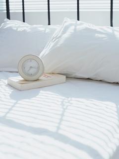 白いベッドと時計