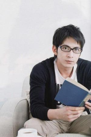 ソファーに腰かけてメガネをかけて読書をする岡田准一
