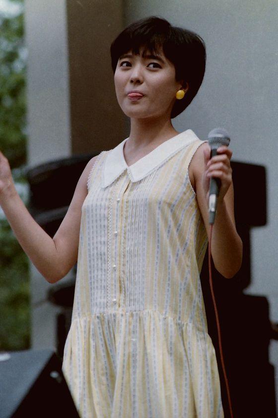 黄色のノースリーブワンピース姿で舌を出すアイドル時代の三田寛子