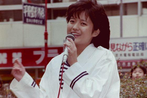 白い大きめのトップスを着て歌うアイドル時代の三田寛子