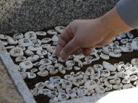 供養塔下に小石の写経を敷く