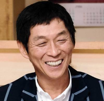 ストライプのスーツを着て微笑んでいる明石家さんまの画像・壁紙