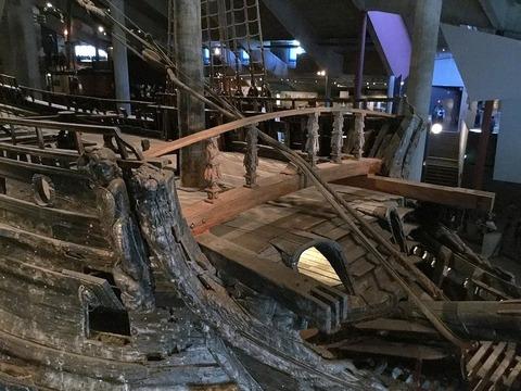 船首上部、復元部分は区別の為に滑らかで明るい木材を使用したX