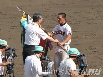 深紅の優勝旗を授与される興南・我如古主将(2010.8.21)