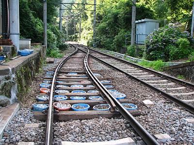 小涌谷駅線路下の編みカゴの中の砂利