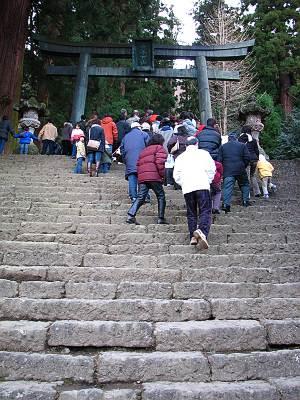 銅鳥居の下まで参詣者の列