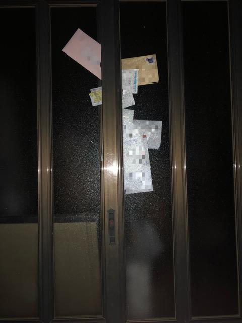 玄関扉に挟まる大量の郵便物
