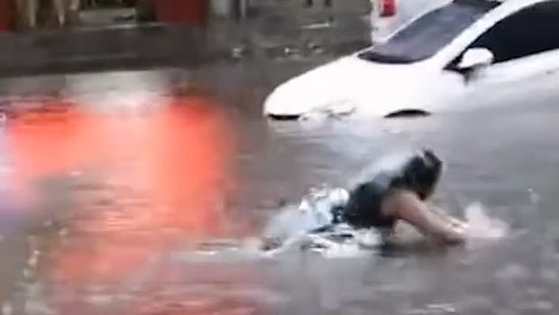 中国、洪水で冠水した道路で水泳する女子、走ってきた車にひかれる!