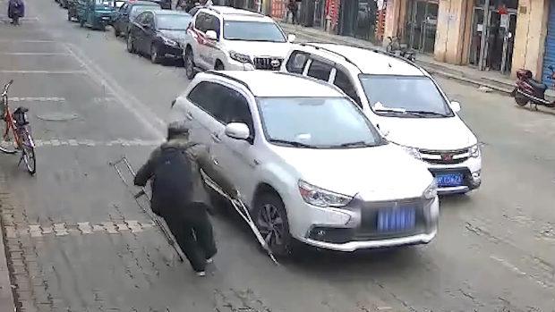 中国、当たり屋のおじいさん、松葉杖を車にちょこんと当てて大げさに倒れる