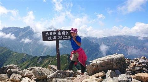山頂で写真を撮る女子小学生