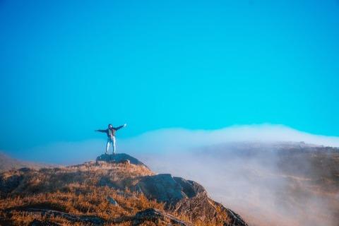 山の頂上でポーズする人