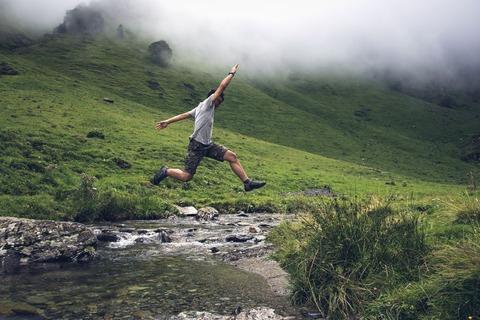 川を飛び越える男性