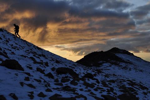 夜明けの中登る登山者