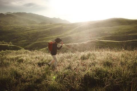 朝陽を浴びて歩く登山者