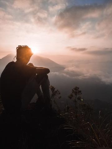 山の頂上で景色を眺める人