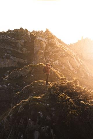山頂で景色の写真を撮る登山者