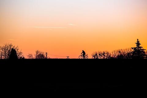 夕暮れに自転車に乗る人